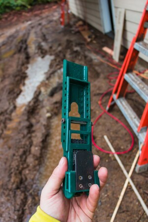 The thin metal piece on the lower back side of the gauge slips under the bottom edge of the last piece of siding.