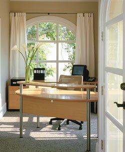 Arched French doors lead into an entry that houses a receptionist desk and waiting area.