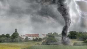 Black tornado funnel and lightning over field during thunderstorm