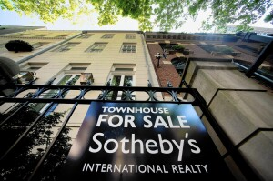 """A Sotheby's """"For Sale"""" sign is displayed outside of a townhouse in New York, U.S., on Monday, June 23, 2014. Americans snapped up previously owned homes in May in the biggest monthly sales gain in almost three years, a sign the residential real estate market is regaining its footing after a stumble early in the year. Photographer: Craig Warga/Bloomberg ** Usable by CT and LA Only **"""