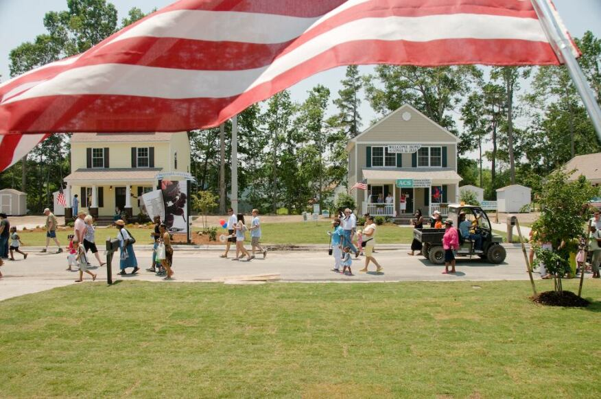 A flag waves from the porch of a newly completed Habitat house in Suffolk, Va., as visitors make their way to dedication ceremonies during Home Builders Blitz 2008.