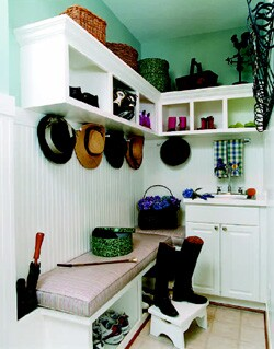 This small 4-foot-by-5-foot mudroom has a place for everything. Architect George Myers designed a built-in bench with storage underneath, an upper row of cubicles, abundant hooks, a sink, and an umbrella stand. He opted for beadboard to protect the walls.