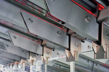 Glass stringer beams rely on the support of load-bearing glass walls to hold the weight of the booth's glowing red staircase and the tourists lounging upon it. The glass pieces are connected with stainless steel brackets and pins, but there is no load-bearing metal in the structure.