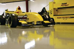 A race car awaits race day on the completed concrete surface.