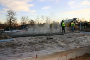 A Purinton Builders crew places a residential foundation slab at dawn on a winter morning. With the appropriate mix design and good control of the concrete temperature in the ready-mix truck, says Purinton, his crews can safely place slabs in freezing weather, without a heated enclosure or sometimes, even blankets.