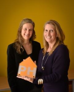 Linda Metropulos, director of housing and neighborhood development at ACTION Housing, (right) receives a Passive House plaque from Katrin Klingenberg, co-founder and executive director of Passive House Institute U.S.