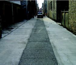 In the alley-center infiltration approach, permeable material (asphalt, concrete, or  pavers) is placed in the center of the alley and high-albedo concrete  is placed along the outer edges. This way, water soaks through the center  of the alley, but truck tires roll on top of the stronger pavement.