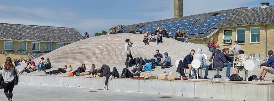 The roof of the gymnasium also serves as a social gathering space in the school's courtyard. Photovoltaic panels mounted on the surrounding rooftops partially power the gymnasium's electric lighting requirements.