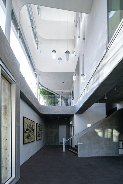 Concrete, metal, and industrial fixtures carry the exterior aesthetic through to the public spaces, such as this lobby that leads to the residential units on the floors above.