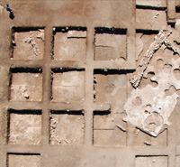 This aerial photo shows the archaeological site at Yifthel. The square excavations are each 16x16 ft., and the 18x40-ft. building footprint with parts of its floor shown is oriented in the direction of the North Star. Mixing and placing concrete to cover the 720 sq. ft. of floor is a major undertaking.