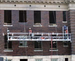 A crew works on a veneer façade. Knowing the latest codes is vital in this kind of work.