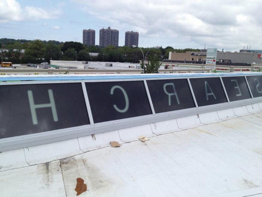 The parapet glass was installed at a 25-degree angle from the vertical axis on the north elevation to catch light from the south. The height of the parapet, from the roof deck to top, is 4 feet 6 inches.