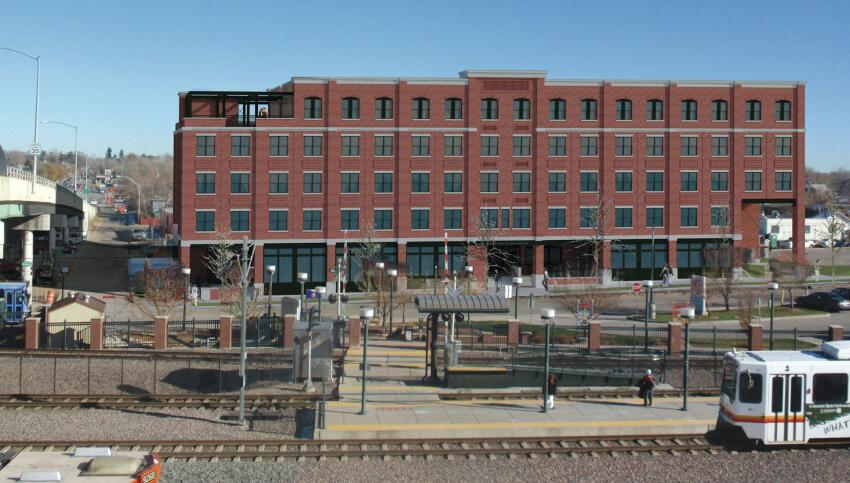 A light-rail station runs just in front of the Evans Station Lofts, an affordable housing project in south Denver designed from the ground up by Parikh Stevens Architects.