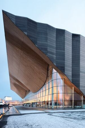 Kilden Performing Arts Centre in Kristiansand, Norway, designed by ALA architects. Kilden's undulating oak façade cantilevers up to 115 feet (35 meters) to hover above the water's edge at its peak.