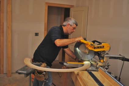 To make the cuts on a miter saw, support the free end of the circular trim in back of you.