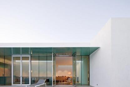 Deep glass soffits cast watery reflections overhead.