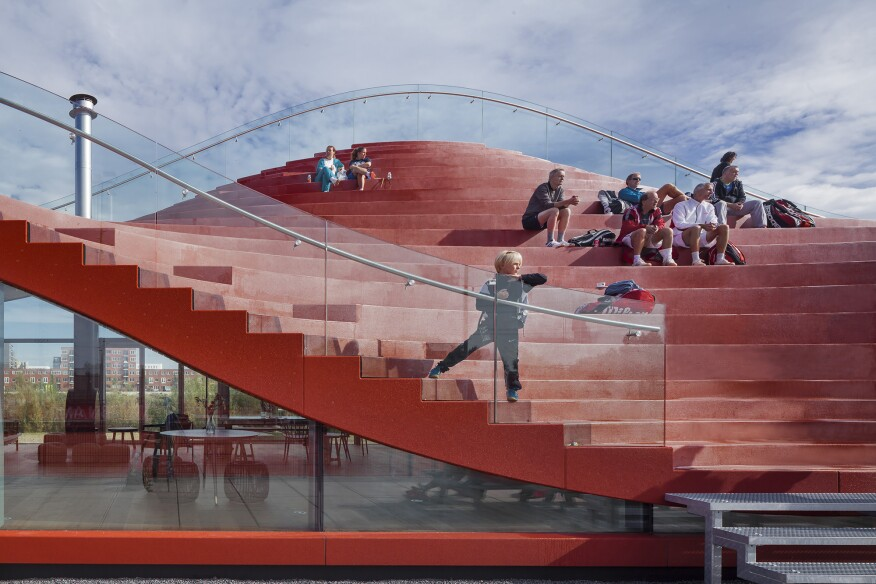 The terraced seating likens an amphitheater setup, but features alternating curves from top to bottom.