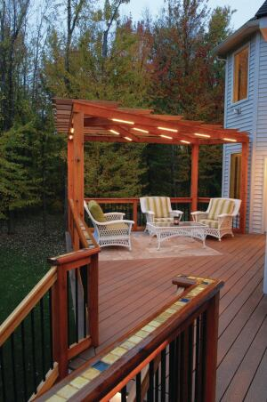 The tile inlay in this cedar rail was installed using offcuts from the deck's travertine tile sitting area (shown in the background), mixed in with pieces from other tile projects.