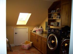 Rather than build out a costly and impractical 40-square-foot laundry room addition, Aurora Custom Remodeling found unused attic space to fill the same purpose. The original laundry space was turned into a mudroom.