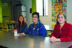 Residents Michelle Hudnall and Mary Jess Darby visit with Rachael Duke, supportive housing program director of Home Forward (from left).