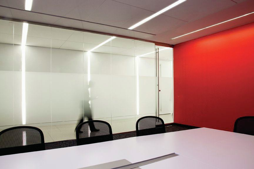 """Lines of light—or """"light frames""""—with minimal detailing, extend from the hallways to interior spaces beyond, such as this small conference room."""