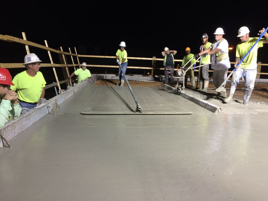 Crew uses a vibrating screed and bull float to finish the test chamber roof slab.