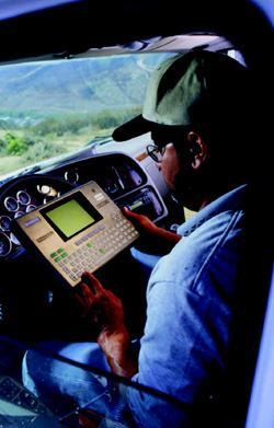 With onboard computers, drivers and dispatchers share information like load  assignments and hours of service while vehicles are out in the field. Here, a  driver has pulled over and is consulting the mobile terminal installed in  his truck's cab.