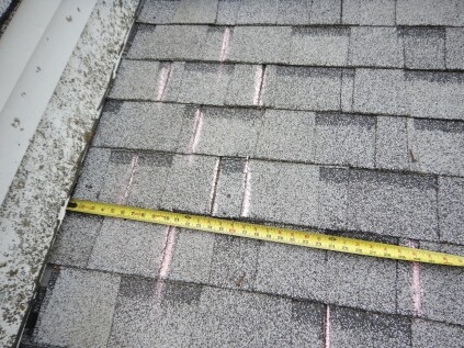 Chalk lines on the roof indicate the breaks in each course of shingles, showing clearly that some of the offsets are less than the required 4-inch minimum, which is set by the shingle manufacturer.