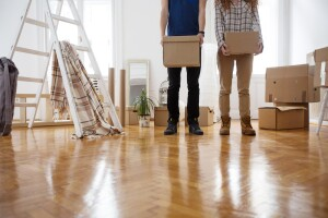 Man and woman holding cardboard boxes as they're moving into a new apartment.