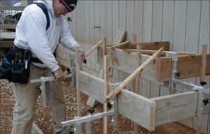 Using Stair-Pro frames allows one person to set the formwork for concrete stairs. Beginning from the top landing, each riser board is hung in place then anchored to stakes and braced.