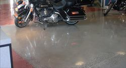 Decorative polished concrete is growing in popularity. Colored dyes were introduced into parts of this floor and the areas near control joints were ground deeper to reveal aggregate in the concrete. The rest of the floor was polished to show the reflection of the motorcycles in the showroom.