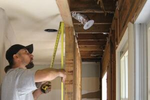 We started by removing cabinets and appliances, then cut back a 2-foot width of ceiling drywall so that we could build a temporary studwall to support the second-floor framing over the kitchen.