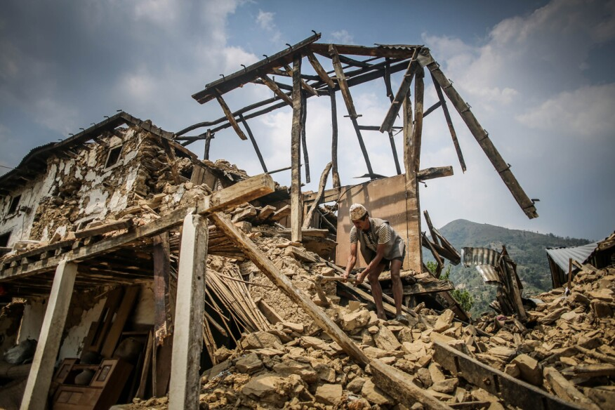 A Nepalese man cleans the rubbles of his destroyed house.