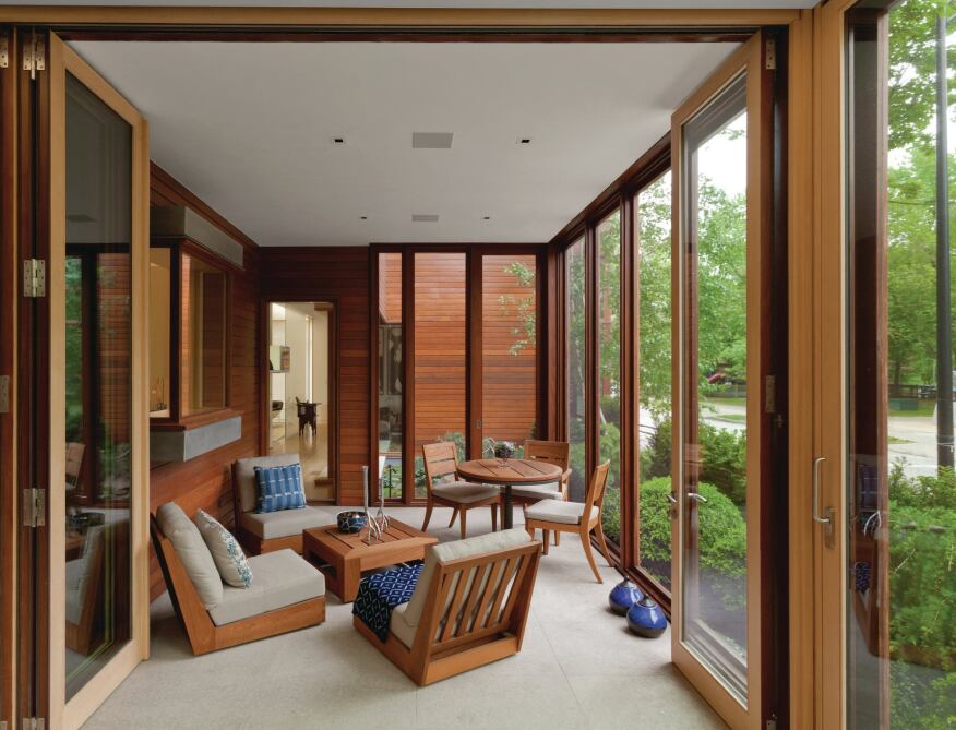 An enclosed porch on the ground floor features views out to the neighborhood through Bendheim glass.