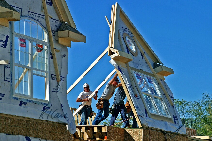Workers push a second-floor, preframed dimension wood exterior wall frame up into position in Ann Arbor, Michigan.