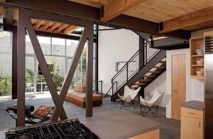 Adams and Smith selected steel for the industrial-style lofts' railings, landings, and exposed cross-bracing (top and above, left.) They inserted volumes for bedrooms and baths (above) into the project's shell (middle).