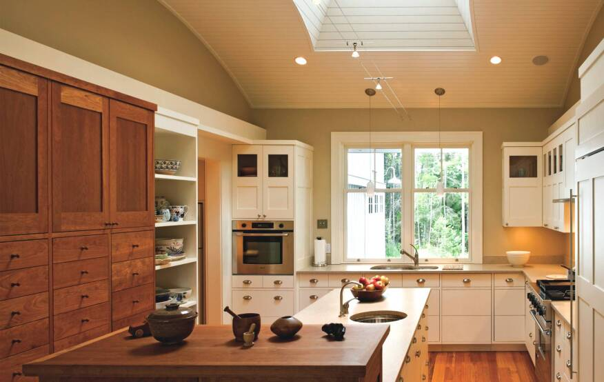 A large central skylight makes this kitchen a magnet for guests and is a boon for cooks with aging eyes.