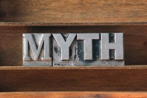 myth word made from metallic letterpress type on wooden tray