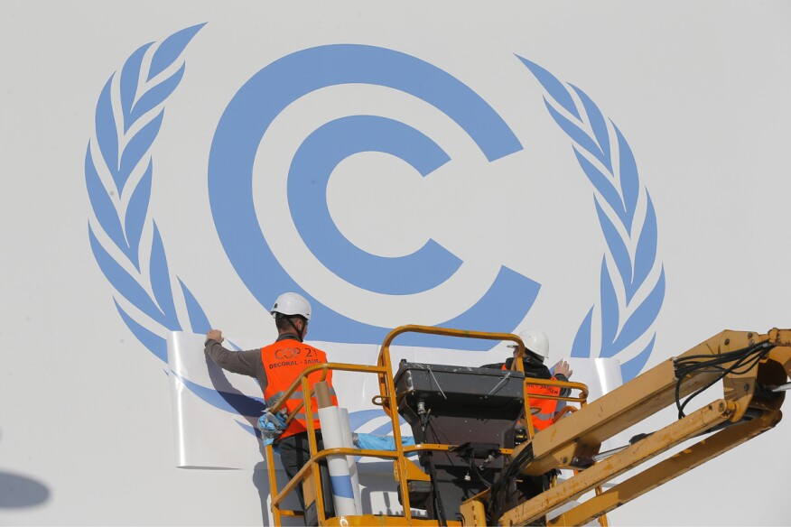 Workers install a logo on the facade of the U.N Climate Conference in Le Bourget, outside Paris.