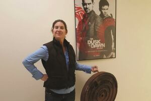 Rebecca Puck Stair, location manager, holding a prop manhole cover she created for a movie shoot in Bernalillo County.