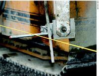 "Stringlines control both the steering for a paving machine and the elevation of the pavement. The horizontal ""wand"" shown here senses elevation and the vertical wand riding on the inside of the line steers the paver."