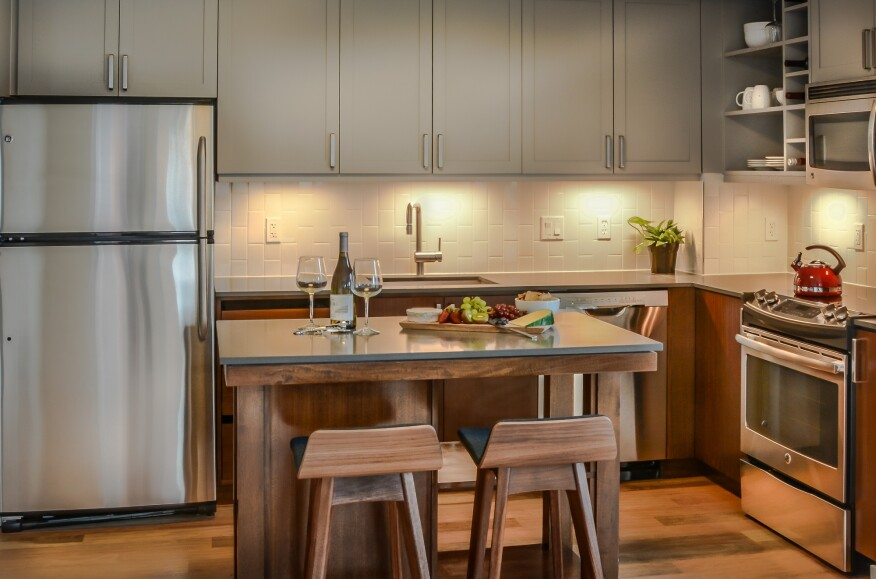 Kitchens at the development offer movable islands, hickory floors, and vertically laid subway tile.