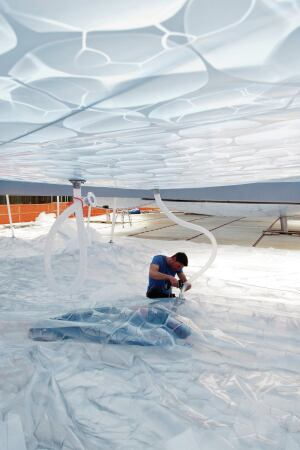 Installing the drainage system between the upper and lower ETFE membrane plies.