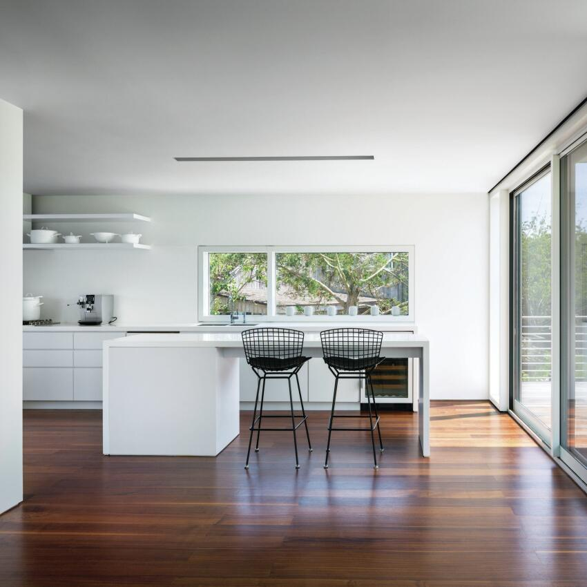 The minimal aesthetic is carried into the all-white kitchen, but wood floors throughout reflect the warm-toned daylight.