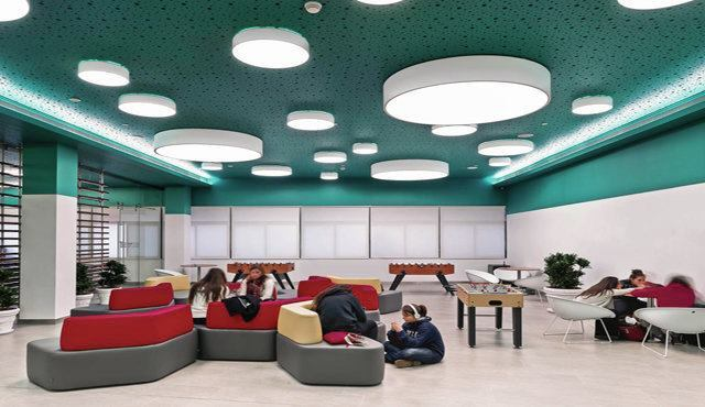 In the lounge, a bold use of color and a playful arrangement of circular-shaped fixtures create a lively setting for students.