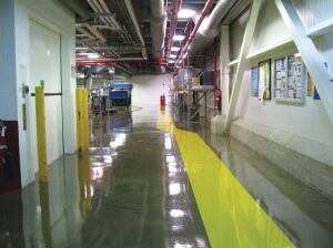The concrete floor of a factory in New Jersey was cured with UV equipment. The yellow coating is the forklift safety stripe. A clear coat was used for the remainder of the floor.