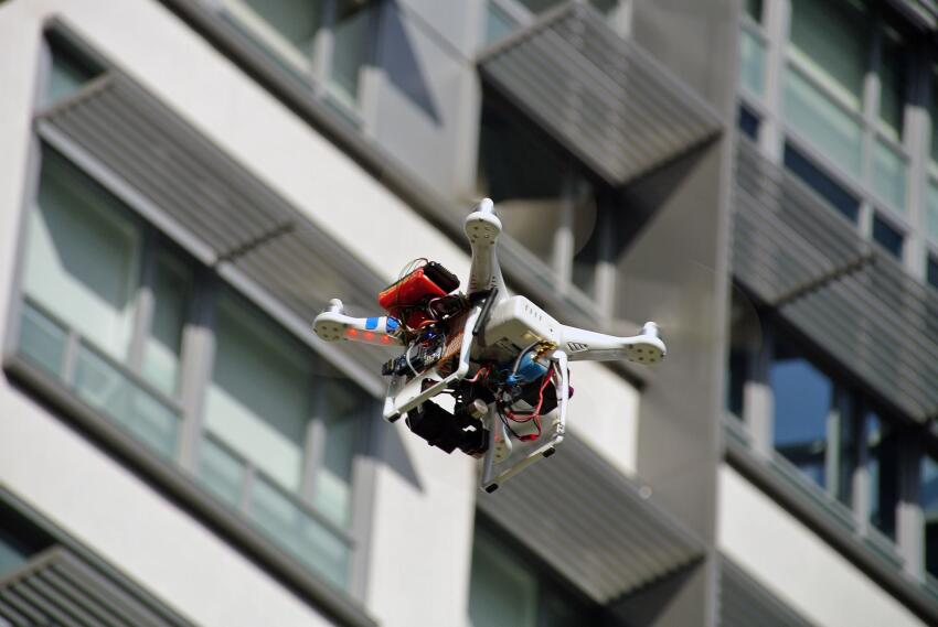 A DJI Phantom drone scans a building at the Chinese University of Hong Kong. The electronics added to the drone include a camera, thermal sensor, GPS device, and wireless transmitter.