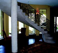 This home adds light to the lower level with a curved wall using the removable concrete forming wall system. The poured-in-place steel-reinforced concrete staircase and the support columns are finished with an ivory-colored plaster coat. The mix is masonry cement and sand with polymer additives. The sand-to-cement ratio creates a suede-like texture. The concrete floor has chemical stain to finish.