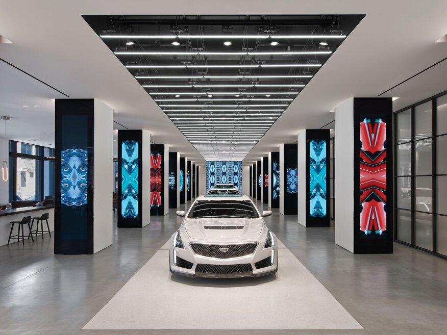 The latest models from Cadillac are displayed on a runway where a combination of light source technologies highlights the automobiles' forms and features.