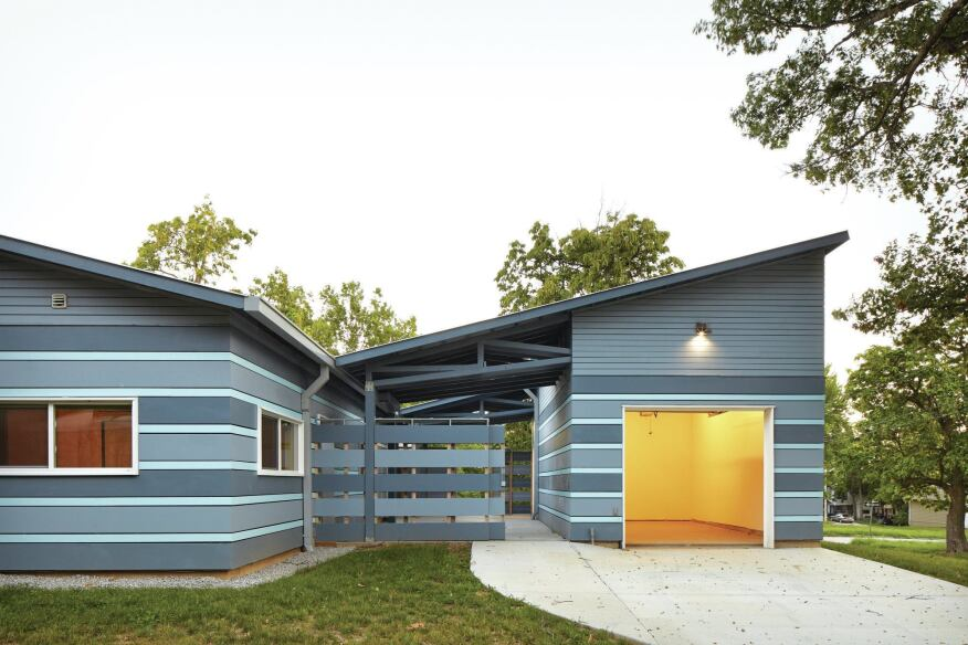 The garage is connected to the house by a set of canted metal roof planes, formed from Firestone Metal Products Una-Clad and Galvalume.